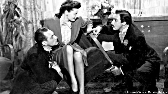 Filmstill aus dem Film Dreimal Komoedie mit drei Darstellern in einem Plausch, eine Frau in der Mitte, zwei befrackte Herren außen