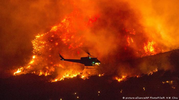 USA Waldbrände in Kalifornien ein Hubschrauber fliegt vor einer Feuerfront