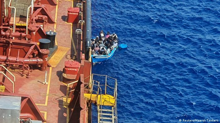 Refugees in a boat by the Maersk Etienne tanker