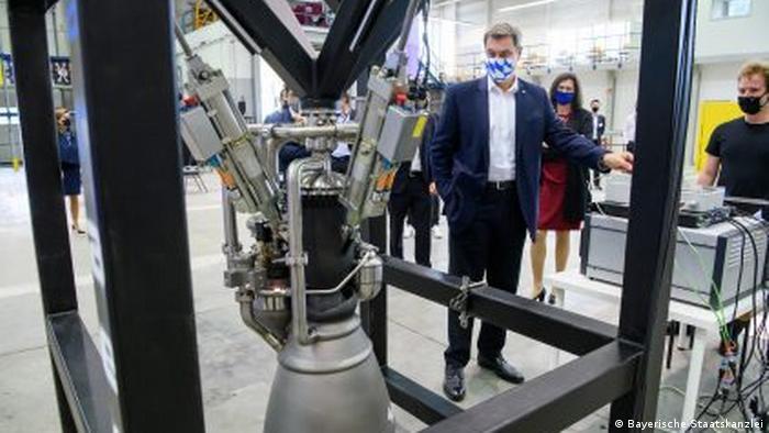 Премьер-министр Баварии Маркус Зёдер осматривает ракетный двигатель, разработанный комапнией Isar Aerospace