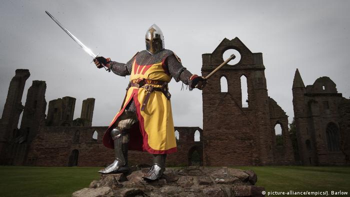 Schottland verkleideter Ritter auf einer Schloss-Ruine