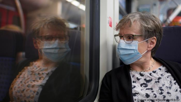 Mulher usando máscara cirurgíca olha o próprio reflexo na janela de um trem