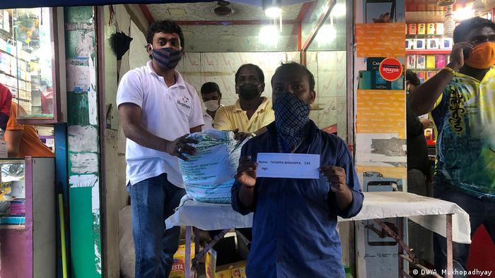 Tayyappa Bhimappa, a migrant worker, receiving his food ration
