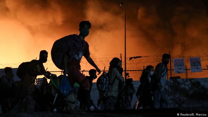 Беженцы идут по дороге вдоль горящего лагеря