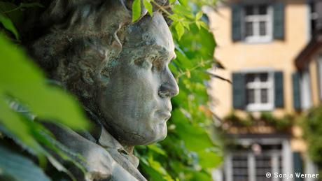 Beethovenkopf zwischen den Blättern einer Hecke