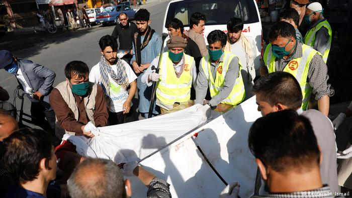 Afghan men carry an injured to a hospital after a blast in Kabul