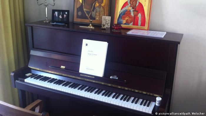 A piano with a score and religious images atop it