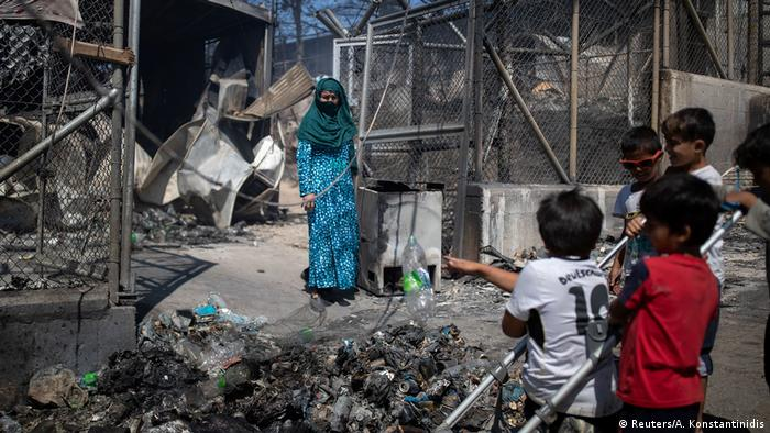 Woman and children in burned-out Moria camp (Reuters/A. Konstantinidis)