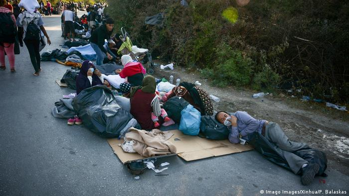 Refugees from a burned-out camp sleep on the road