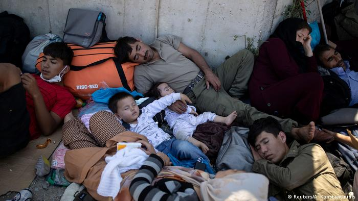 Refugees lie on blankets and bags on the ground under the open sky