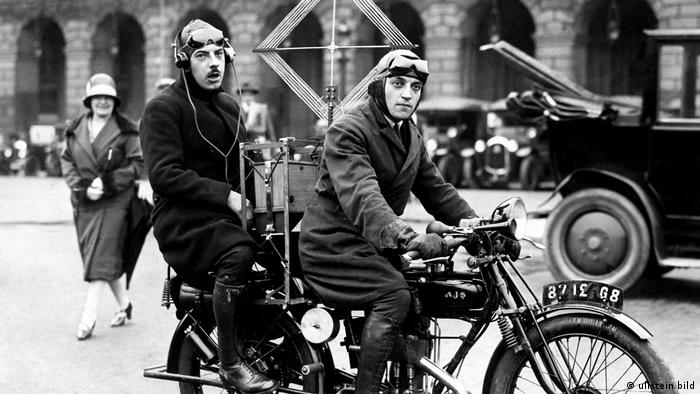 Black and white photo from 1928: Two men on a motorcycle listening to the radio with earphones connected to a bulky device with antenna; a woman is smiling in the background