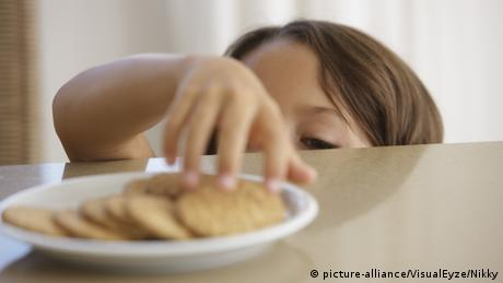 A child taking a cookie from a plate on a table
