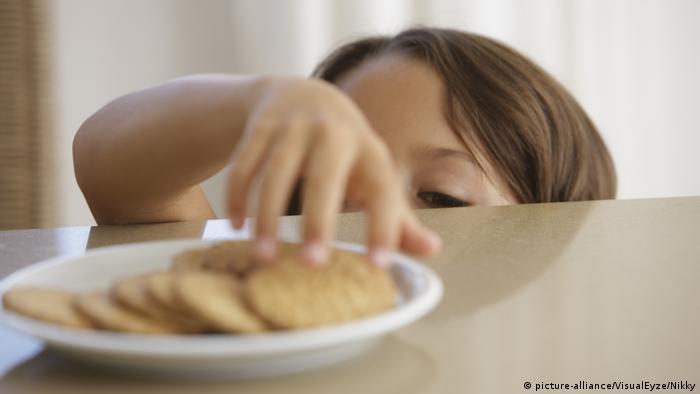 Ein Kind nimmt einen Keks von einem Teller auf dem Tisch (picture-alliance/VisualEyze/Nikky)