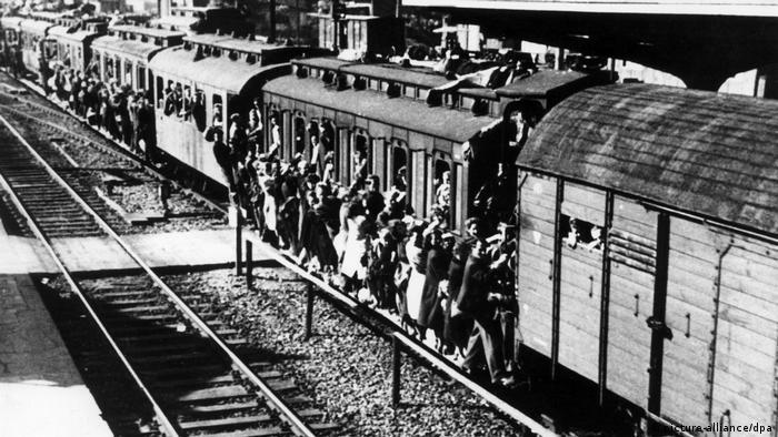 Blick auf einen überfüllten Zug, draußen hängen Menschen (picture-alliance/dpa)