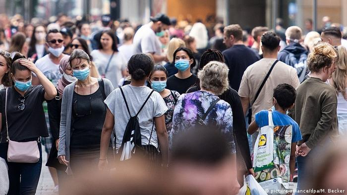 People with facemasks in pedestrian shopping street (picture-alliance/dpa/M. Becker)