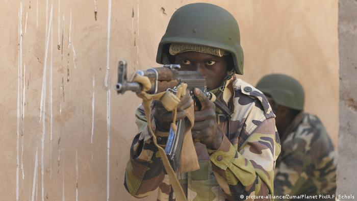 A Nigerien soldier takes aim with a rifle