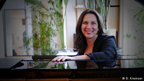 Pianistin Susanne Kessel sitzt an ihrem Flügel und lächelt in die Kamera.