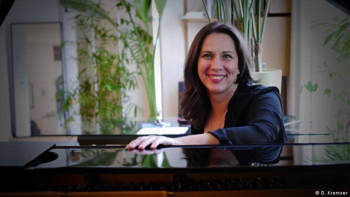 Pianistin Susanne Kessel sitzt an ihrem Flügel und lächelt in die Kamera. (D. Kremser)