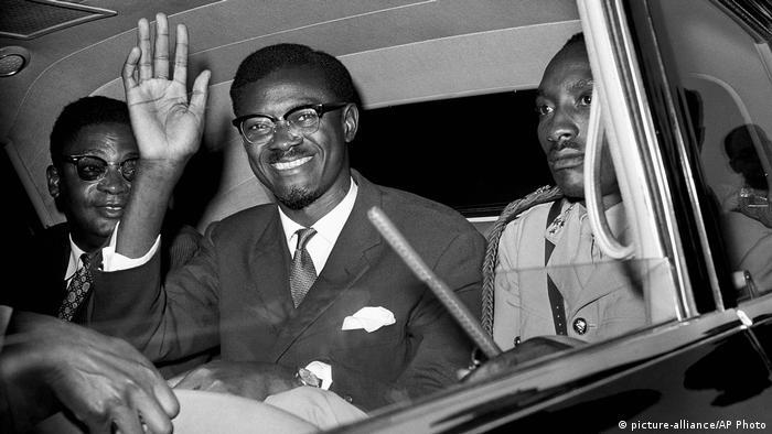 Líder congolês Patrice Lumumba sorri e acena de dentro de automóvel