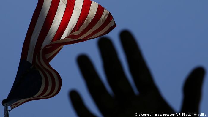 Рука, тянущаяся к флагу США