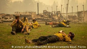 Пожарные отдыхают возле сгоревшего здания