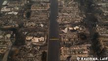 A person walks past gutted homes in the Medford Estates neighborhood in the aftermath of the Almeda fire in Medford, Oregon, U.S., September 10, 2020. Image taken with a drone. REUTERS/Adrees Latif