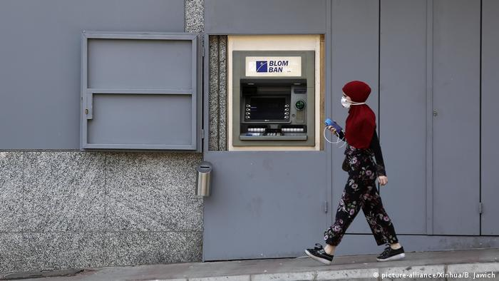 A woman walks past an ATM in Beirut