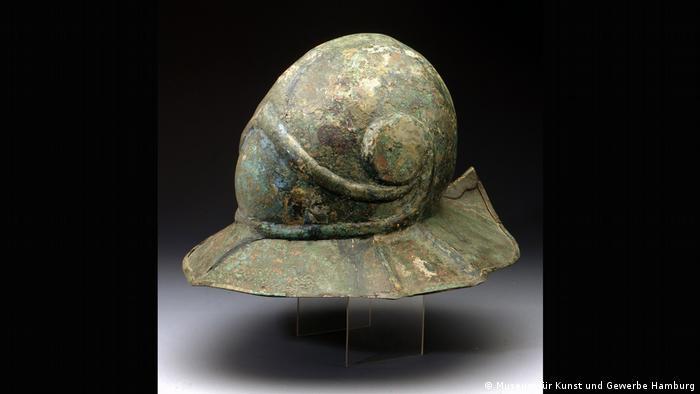 A metal helmet with a swirl-shaped decoration and a wide brim.  (Museum für Kunst und Gewerbe Hamburg)