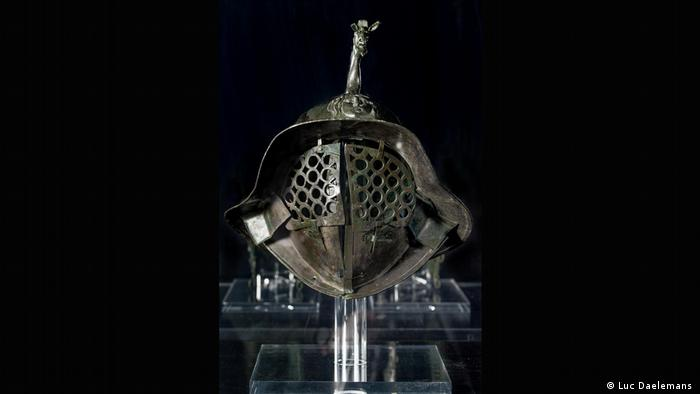 A helmet with a metal cage-like contraption as an eye covering and a decorative animal sculpture on top. (Luc Daelemans)