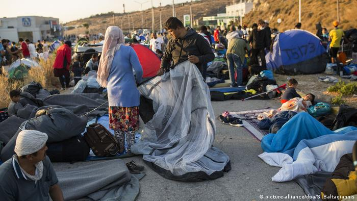People on the ground along the side of a road on the Greek island of Lesbos