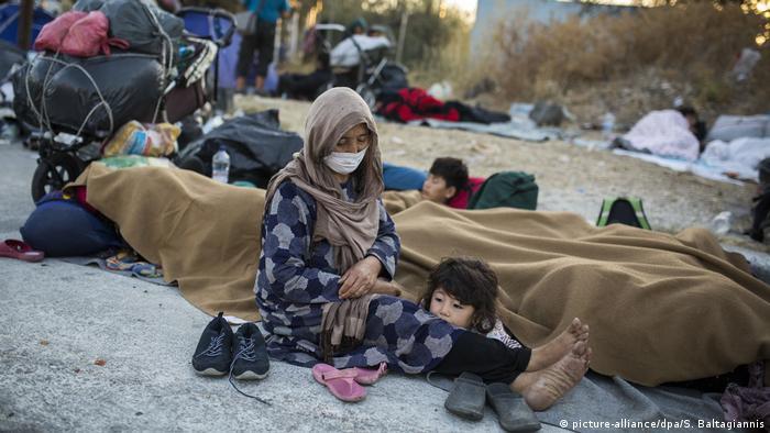 Mulher com crianças sentados em terreno arenoso