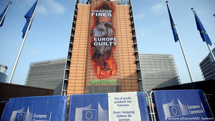 Faixa gigante na sede da Comissão Europeia, em Bruxelas, com imagens da Amazônia em chamas e a frase Amazônia está queimando, Europa é culpada