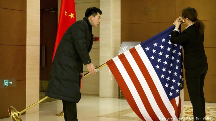 Zwei Chinesische Mitarbeiter justieren eine US-Flagge