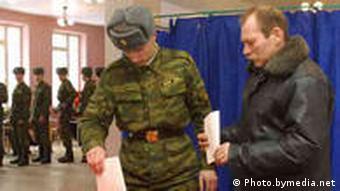 Солдат бросает бюллетень в избирательную урну