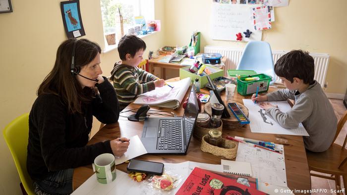 Mujer que trabaja desde casa mientras sus dos hijos se sientan en la misma mesa