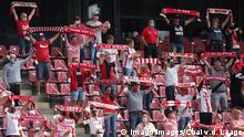 Cologne FC fans holding club scarves up in stadium (Imago Images/Chai v.d. Laage)
