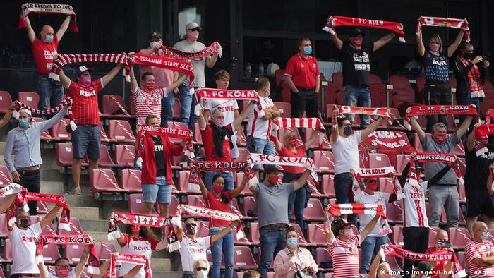 Cologne FC fans holding club scarves up in stadium