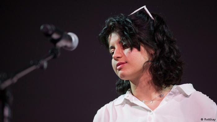Nahaufnahmer einer jungen Frau in einem weißen Hemd vor einem Mikrophon (Rottkay)