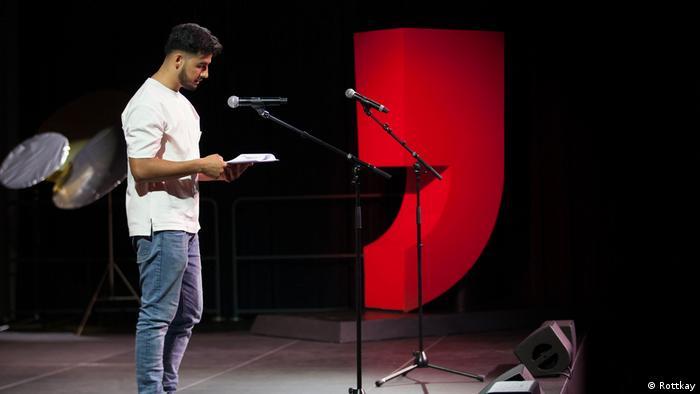 Ein junger Mann mit Jeans und weißem T-Shirt steht auf der Bühne vor einem Mikrophon mit einem Papier in der Hand (Rottkay)