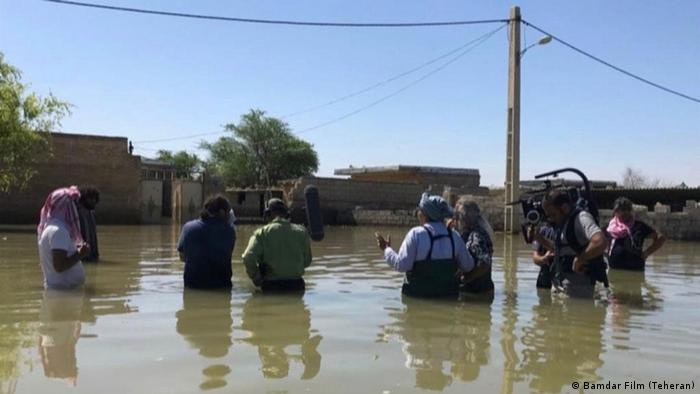 Crew-Mitglieder stehen bis zum Bauch im Wasser (Bamdar Film (Teheran))