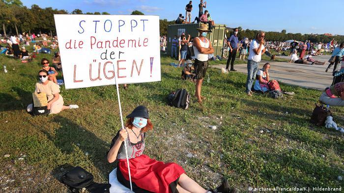 Manifestante sentada no chão segura um cartaz com os dizeres, em alemão: Pare a pandemia das mentiras