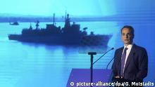Griechenlands Premier Kyriakos Mitsotakis, bei einer TV-Rede zum griechischen Aufrüstungsprogramm nationales Schild im September 2020. Im Hintergrund sieht man die Silhouetten von Kriegsschiffen, die Griechenland im Konflikt mit der Türkei schützen sollen.