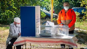 Урна с избирательными бюллетенями установлена на столе на улице, рядом два человека