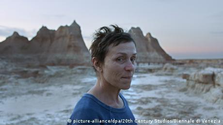 Frances McDormand als Fern steht am Meeresufer, im Hintergrund Felsen.
