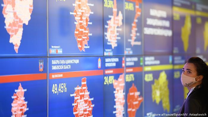 Женщина в маске смотрит на экраны в информационном центре ЦИК России