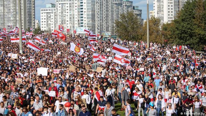 Multidão ergue bandeiras nas cores vermelha e branca