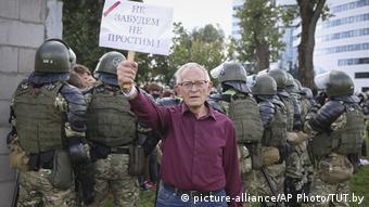 Человек держит плакат с надписью: Не забудем, не простим
