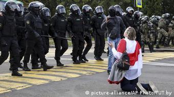 Протестующая женщина в Минске на коленях перед шеренгой силовиков