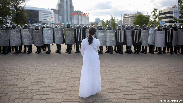 Женщина в белом платье стоит одна перед шеренгой омоновцев в касках и со щитами