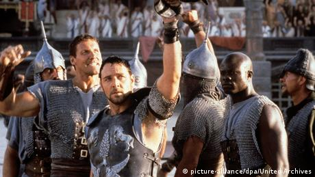 A still from Ridley Scott's 'Gladiator': Russel Crowe and a group of gladiator actors show raised fists (picture-alliance/dpa/United Archives)
